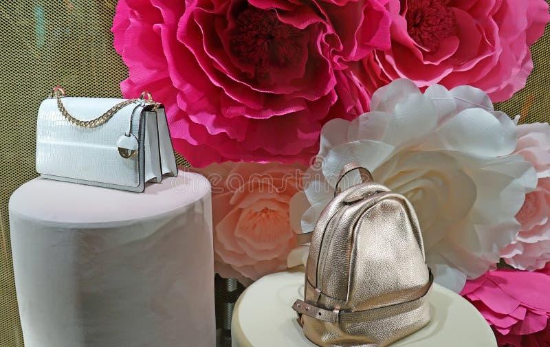 Moderna handväskor i ett shoppafönster på bakgrund av rosor Oroton är för modetillbehör för australier ett lyxigt företag royaltyfria bilder
