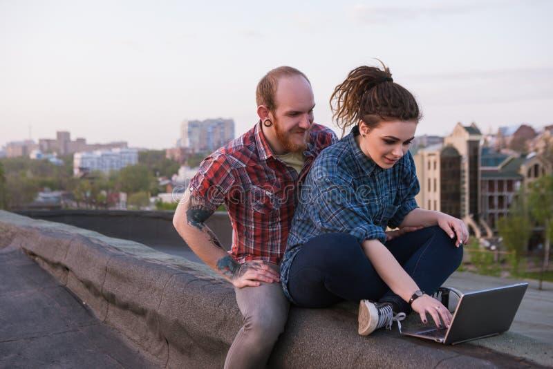 Moderna hipsterungdompar på taket royaltyfria bilder