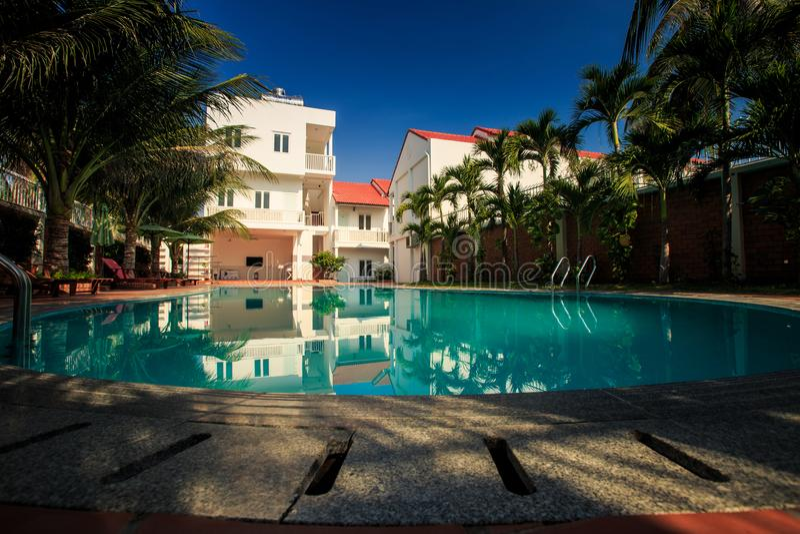 Moderna hus för semesterorthotell reflekterar i blått vatten för pöl royaltyfri foto