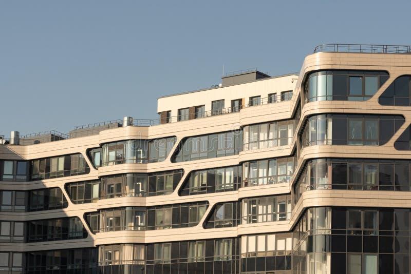 Moderna hyreshusar p? en solig dag med en bl? himmel Fasad av en modern hyreshus royaltyfria foton