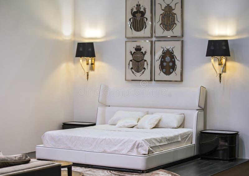 Moderna inre, vita sovrum med dubbla sängar, målningar och lampor på väggarna Den vackra utformningen av sovrummet arkivbild