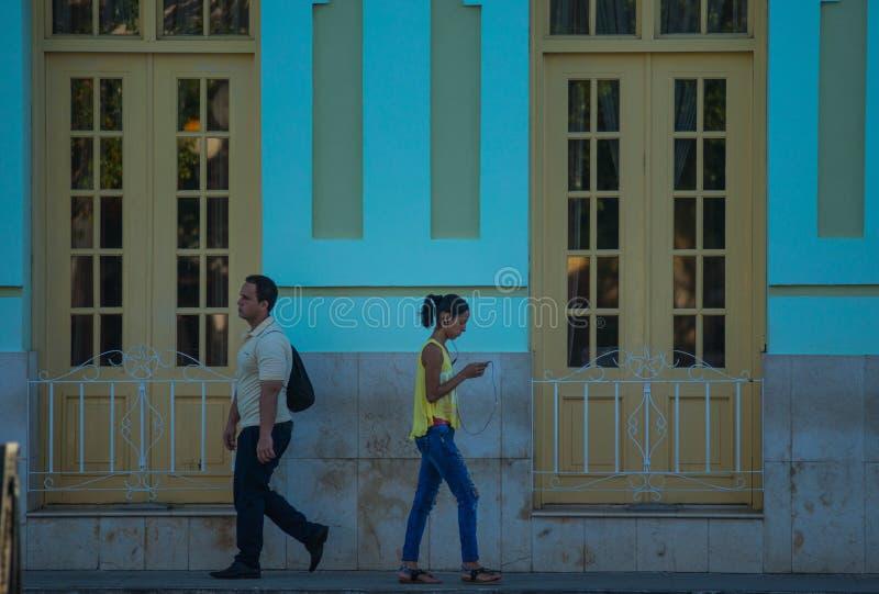 Moderna kubanska ungdomarsom går i gata av den koloniala staden för karibisk färgrik kommunism, havannacigarr, Kuba, Amerika arkivbilder