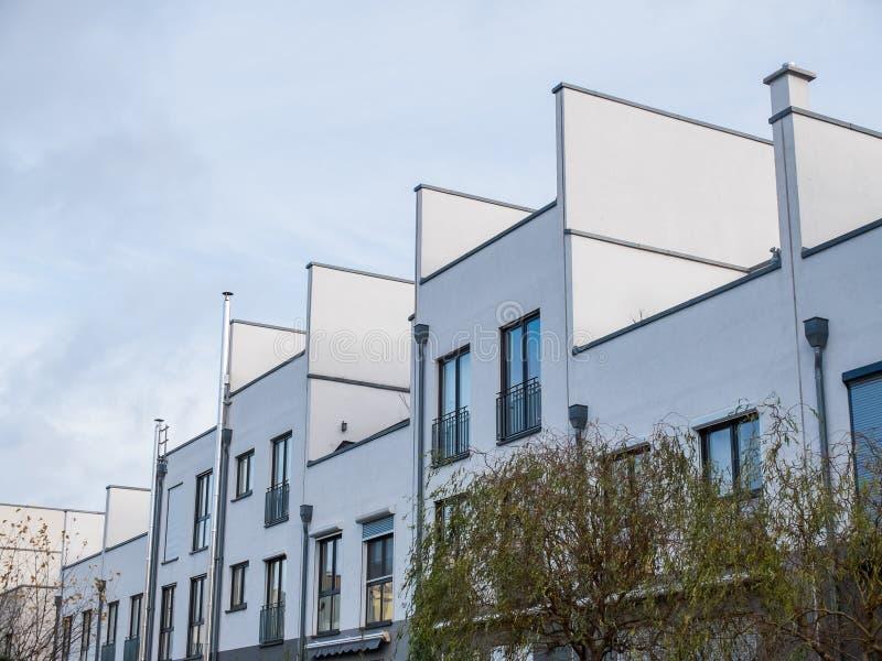 Moderna låga löneförhöjningradhus med takuteplatser royaltyfri foto