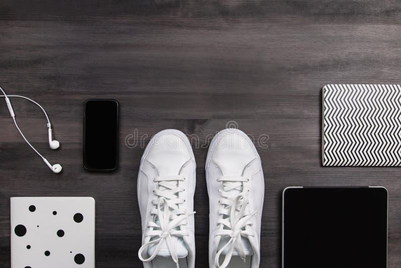 Moderna män danar tillbehör och elektroniska apparater på mörk bakgrund Den vita gymnastiksko-, minnestavla- och telefonlägenhete fotografering för bildbyråer