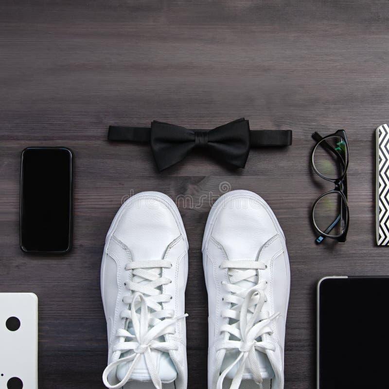 Moderna män danar tillbehör och elektroniska apparater på mörk bakgrund Den vita gymnastiksko-, minnestavla- och telefonlägenhete royaltyfria foton