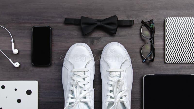 Moderna män danar tillbehör och elektroniska apparater på mörk bakgrund Den vita gymnastiksko-, minnestavla- och telefonlägenhete arkivbilder