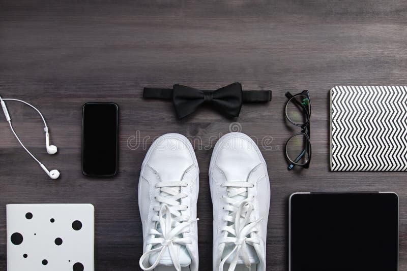 Moderna män danar tillbehör och elektroniska apparater på mörk bakgrund Den vita gymnastiksko-, minnestavla- och telefonlägenhete arkivfoton