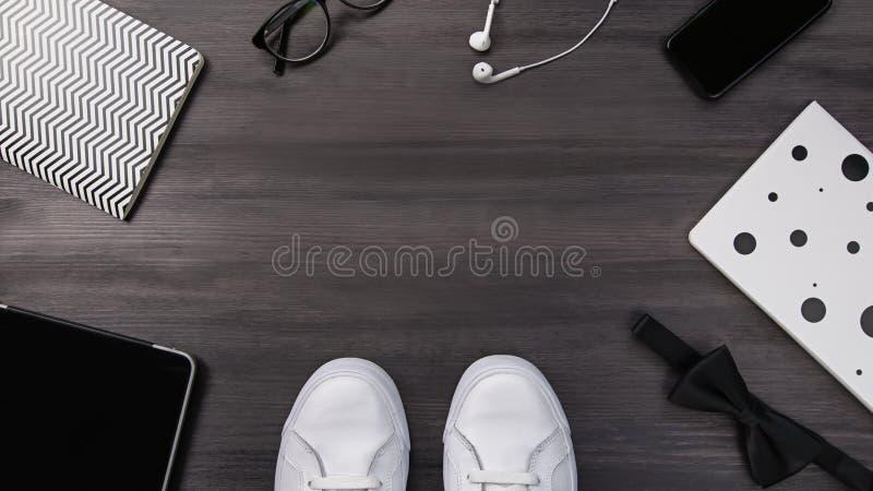 Moderna män danar tillbehör och elektroniska apparater på mörk bakgrund Den vita gymnastiksko-, minnestavla- och telefonlägenhete arkivbild