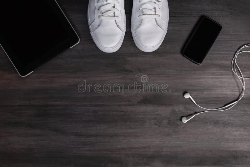 Moderna män danar tillbehör och elektroniska apparater på mörk bakgrund Den vita gymnastiksko-, minnestavla- och telefonlägenhete royaltyfria bilder