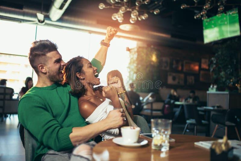Moderna par i kafét som ser fotbollsmatchen på tv i kafé royaltyfri fotografi