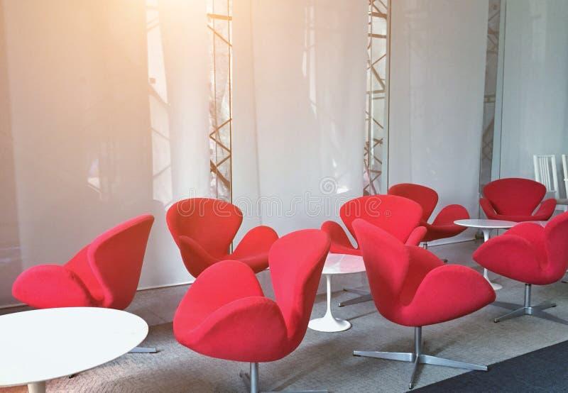 Moderna röda stolar i mötesrummet för lyssnande perioder royaltyfri bild