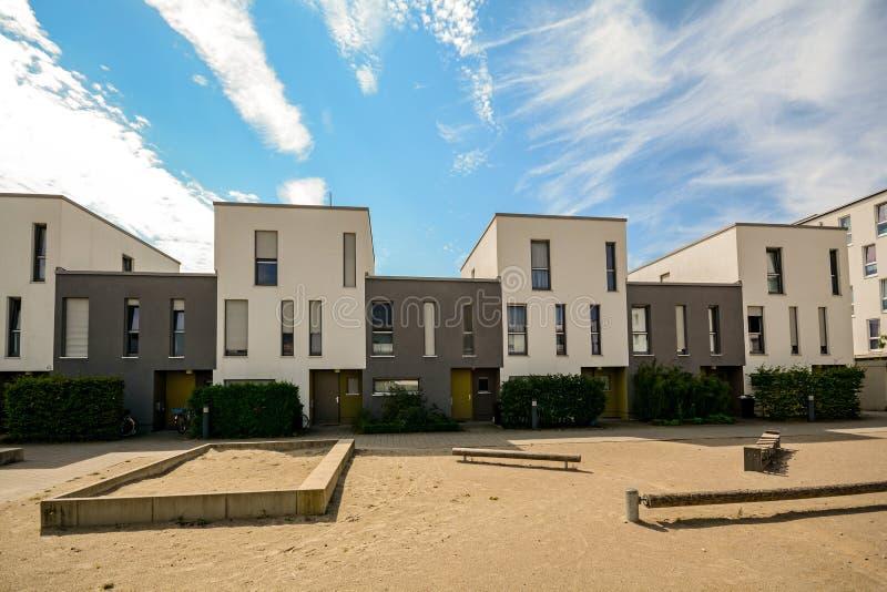 Moderna radhus i ett bostadsområde, nya hyreshusar med gröna utomhus- lättheter i staden royaltyfria bilder