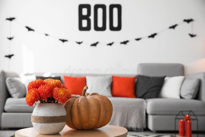 Moderna rum dekorerade för Halloween, med fokus på bord med pumpa och blommor royaltyfri bild