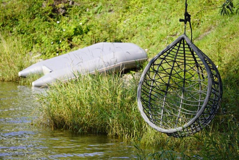 Moderna silla de descanso exterior colgante sobre el agua, un bote de goma para pescar peces estacionados en la orilla. vida de la fotografía de archivo libre de regalías