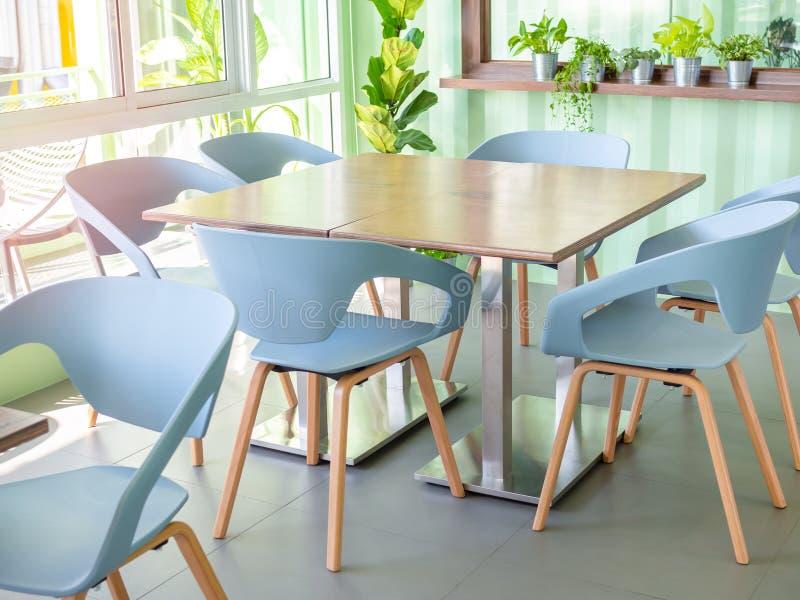 Moderna stolar och trätabell i kafé fotografering för bildbyråer