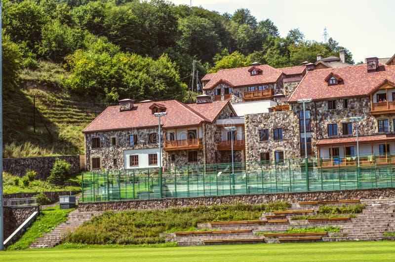 Moderna stugor för studenter, med sned träbalkonger i etnisk stil och bekväma tennisbanor på internationellt Co arkivfoto