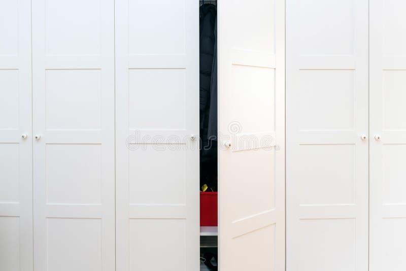 Moderna vita träkabinetter i sovrummet med en öppnad dörr royaltyfri fotografi