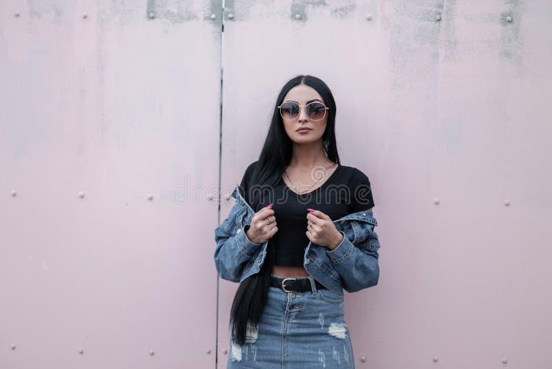 Moderna y bella hipster mujer con elegantes gafas negras de sol se pone de pie y endereza una chaqueta de moda de denim cerca de  fotos de archivo libres de regalías