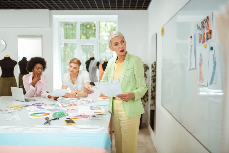 Moderne ältere Blondinestellung in einer Werkstatt lizenzfreie stockbilder