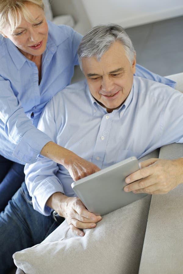 Moderne ältere Paare unter Verwendung der Tablette stockfotografie