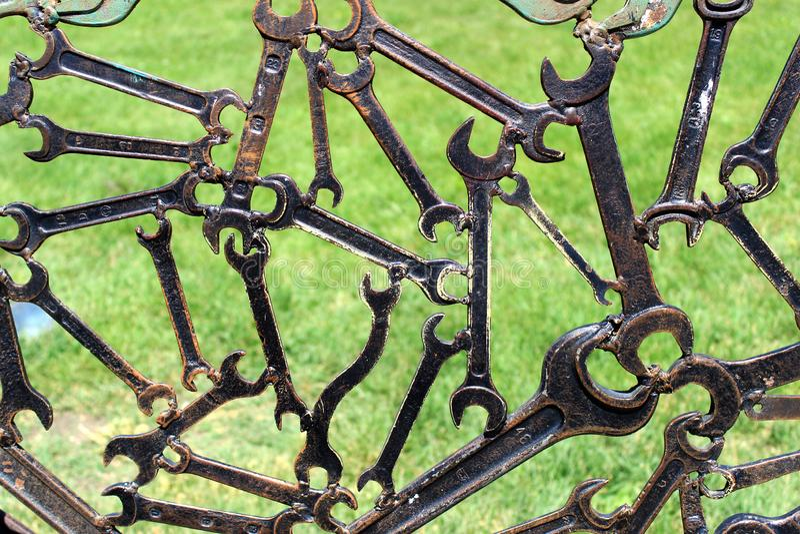 Moderne abstracte industriële achtergrond van gelaste metaalmoersleutels met erachter gras stock fotografie