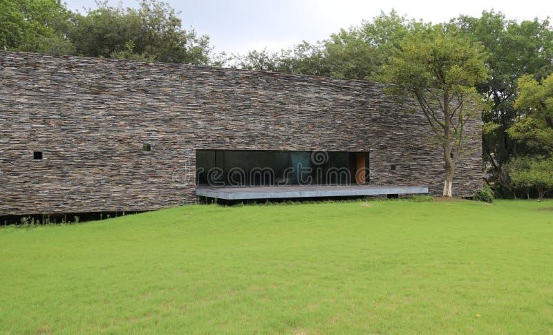 Moderne Architektur Im Freienlandschaft Ein Gebäude mit Steinwänden auf dem Gras lizenzfreie stockfotos