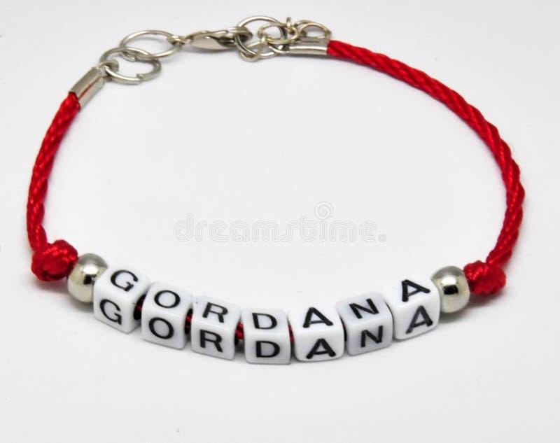 Moderne armband met namen op een rode vlecht op een witte achtergrond royalty-vrije stock afbeeldingen