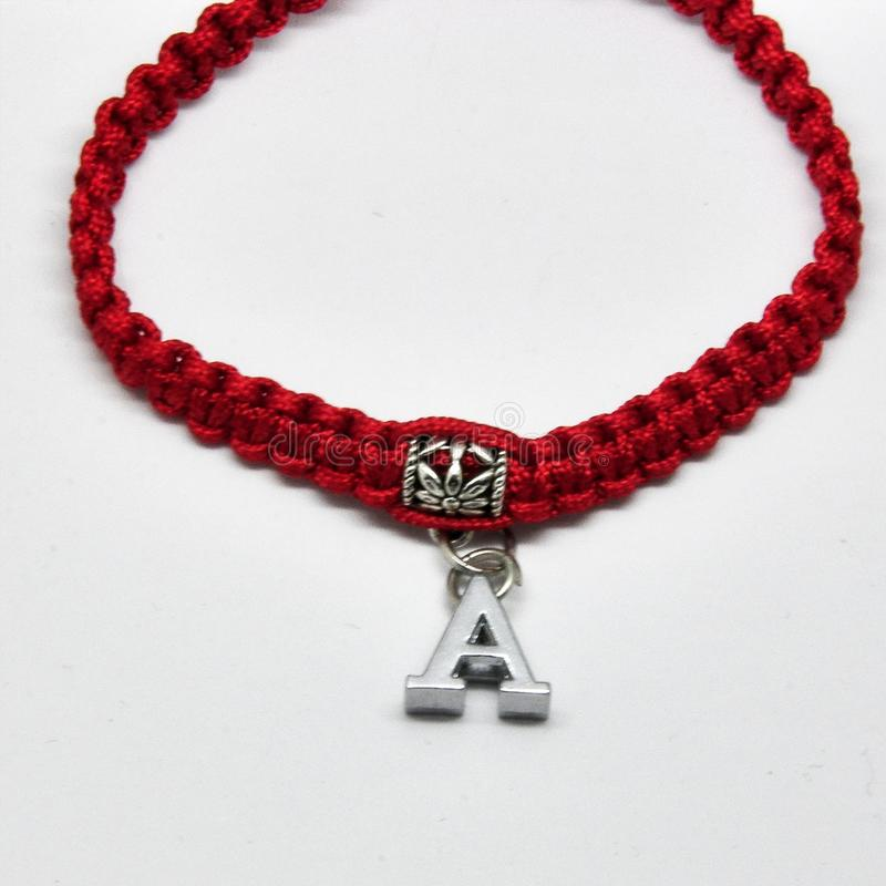 Moderne armband met namen op een rode vlecht op een witte achtergrond stock foto