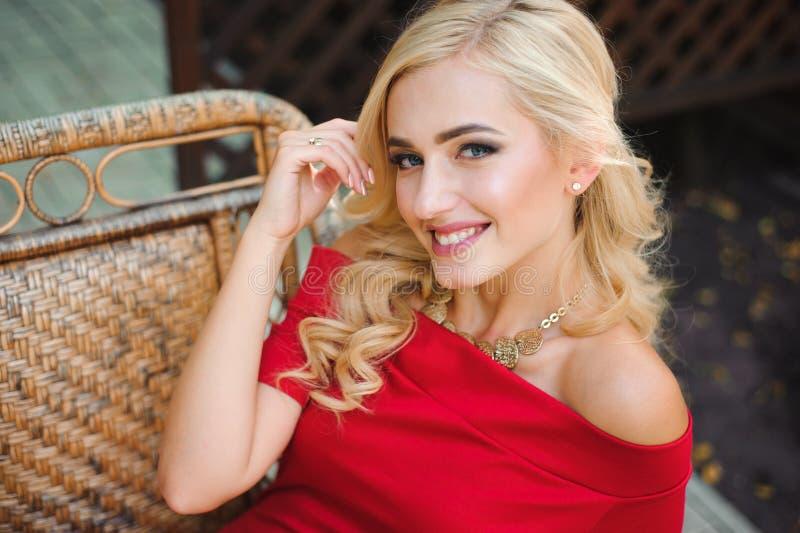 Moderne attraktive Blondine im roten Kleid, das auf Stuhl sitzt stockfoto