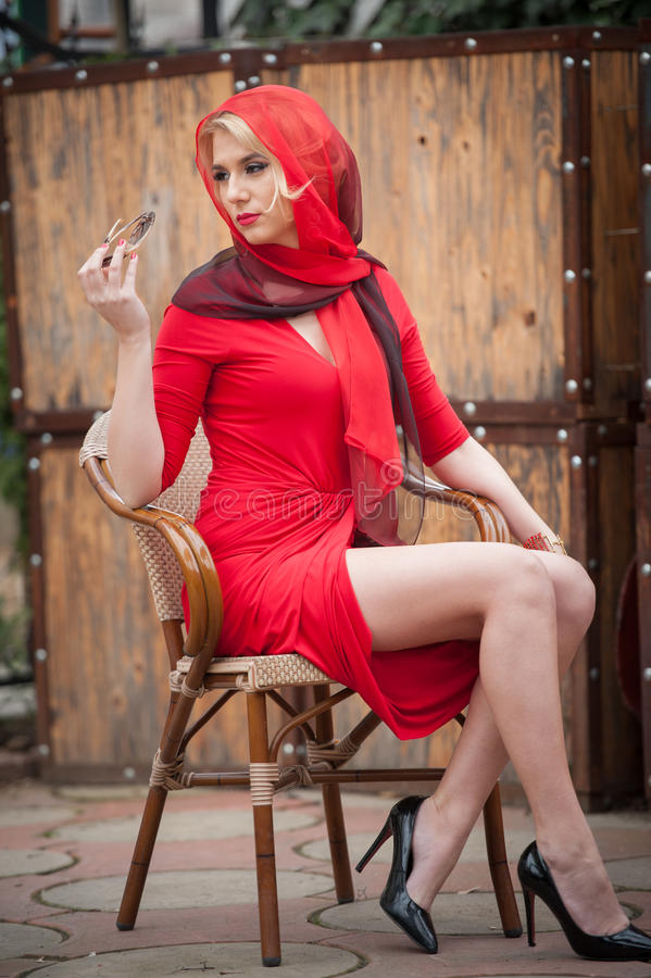 Moderne attraktive Blondine im roten Kleid, das auf Stuhl sitzt Schöne elegante Frau mit dem roten Schal, der in der eleganten Sz stockfoto