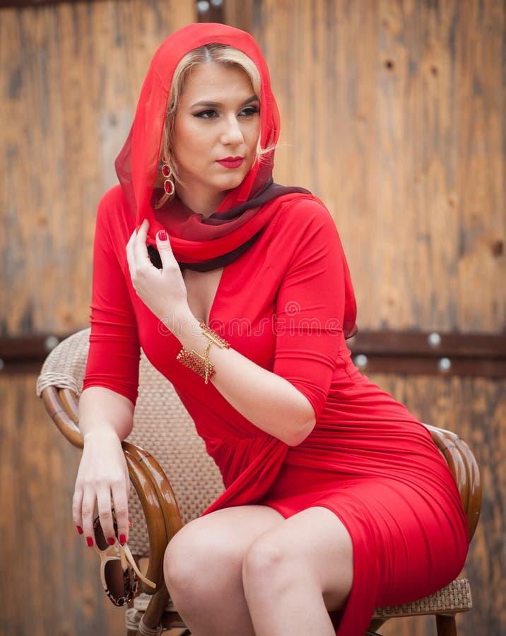 Moderne attraktive Blondine im roten Kleid, das auf Stuhl sitzt Schöne elegante Frau mit dem roten Schal, der in der eleganten Sz stockbild