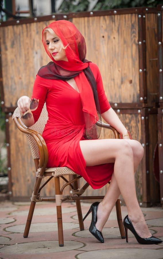 Moderne attraktive Blondine im roten Kleid, das auf Stuhl sitzt Schöne elegante Frau mit dem roten Schal, der in der eleganten Sz stockbilder