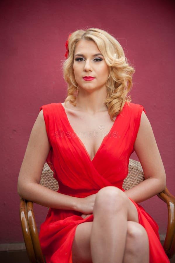 Moderne attraktive Blondine im roten Kleid, das auf Stuhl sitzt Schöne elegante Frau mit roter Blume bei der Haaraufstellung lizenzfreies stockbild