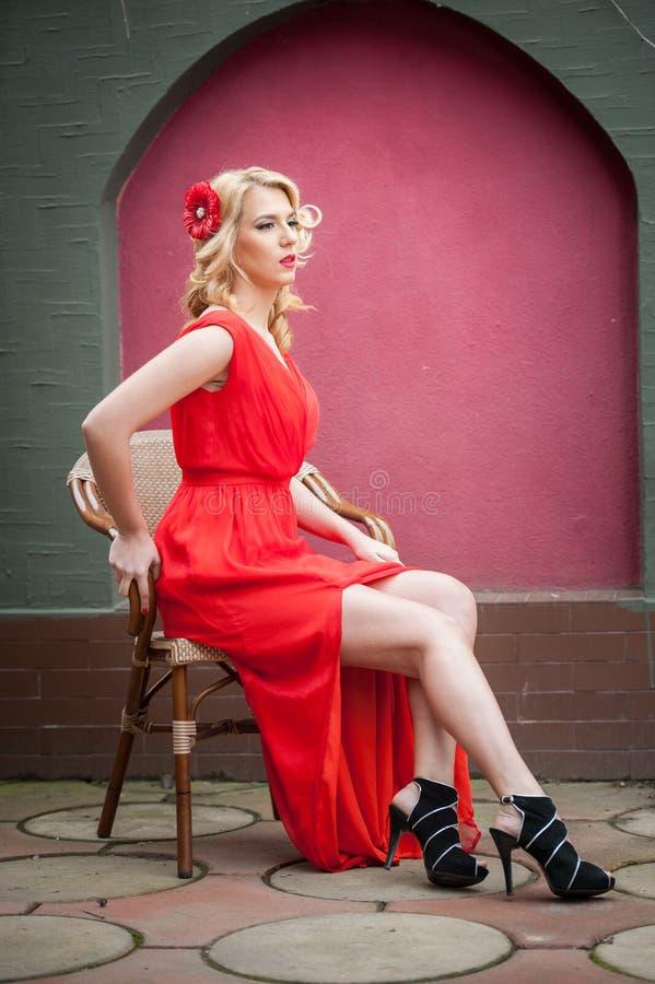 Moderne attraktive Blondine im roten Kleid, das auf Stuhl sitzt Schöne elegante Frau mit roter Blume im Haar, das im eleg aufwirf stockbild