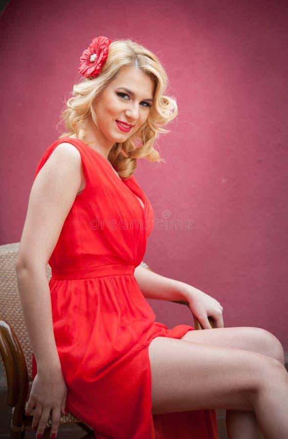 Moderne attraktive Blondine im roten Kleid, das auf Stuhl sitzt Schöne elegante Frau mit roter Blume im Haar, das im eleg aufwirf stockbilder