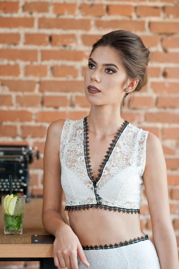 Moderne attraktive Dame mit dem weißen Kleid, das nahe einer Restauranttabelle etwas trinkt steht Kurzes Haar Brunettefrau stockbilder