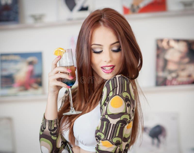 Moderne attraktive junge Frau im farbigen Kleid, das ein Glas und ein Lächeln hält Schöne Rothaarige, die in der eleganten Landsc stockbild