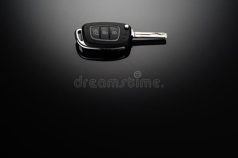 Moderne Autoschlüssel lokalisiert auf schwarzem reflektierendem Hintergrund lizenzfreie stockfotografie