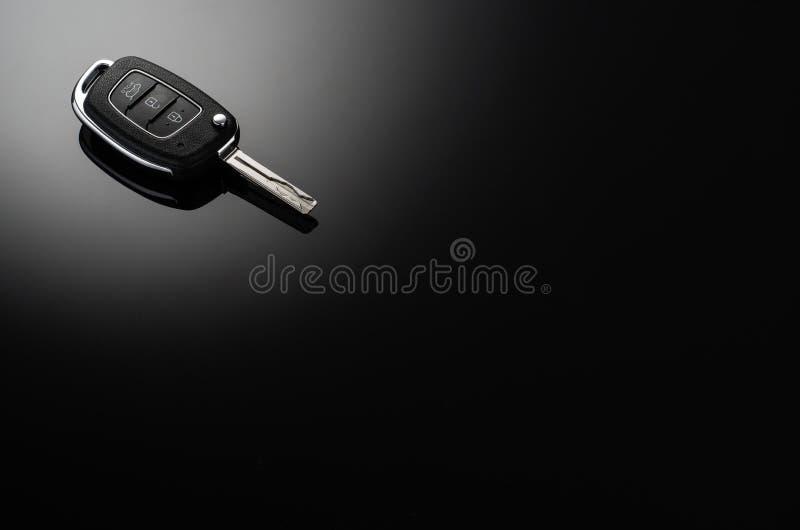 Moderne Autoschlüssel lokalisiert auf schwarzem reflektierendem Hintergrund stockbild