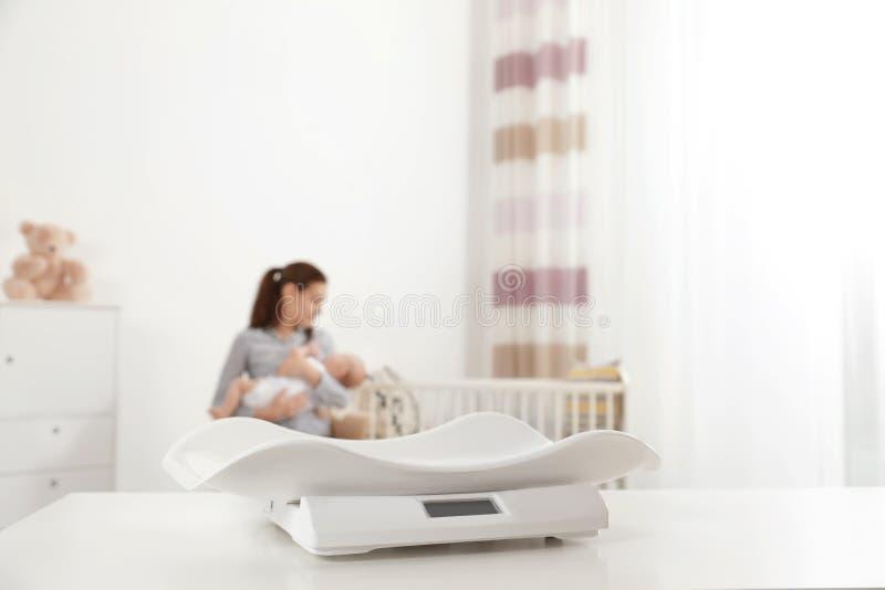 Moderne babyschalen op lijst en vage vrouw met kind binnen royalty-vrije stock fotografie