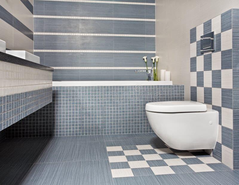 Moderne badkamers in blauwe en grijze tonen met toilet stock afbeelding