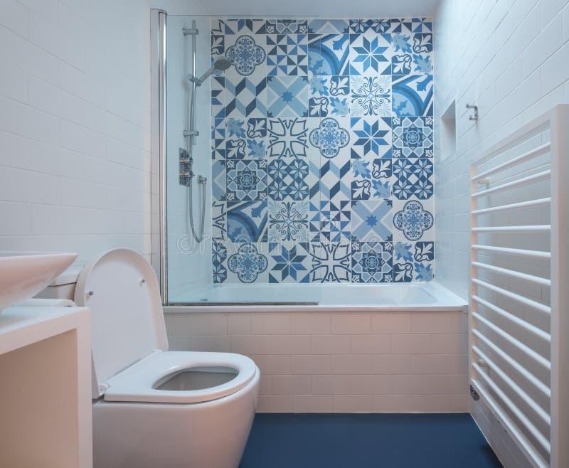 Moderne badkamers met bad, toilet, gebied in muur en bassineenheid, blauwe rubbervloer en blauwe en witte lapwerktegels royalty-vrije stock foto's