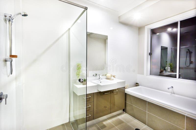 Moderne badkamers met een tapkraan, een waterton en vloertegels stock foto