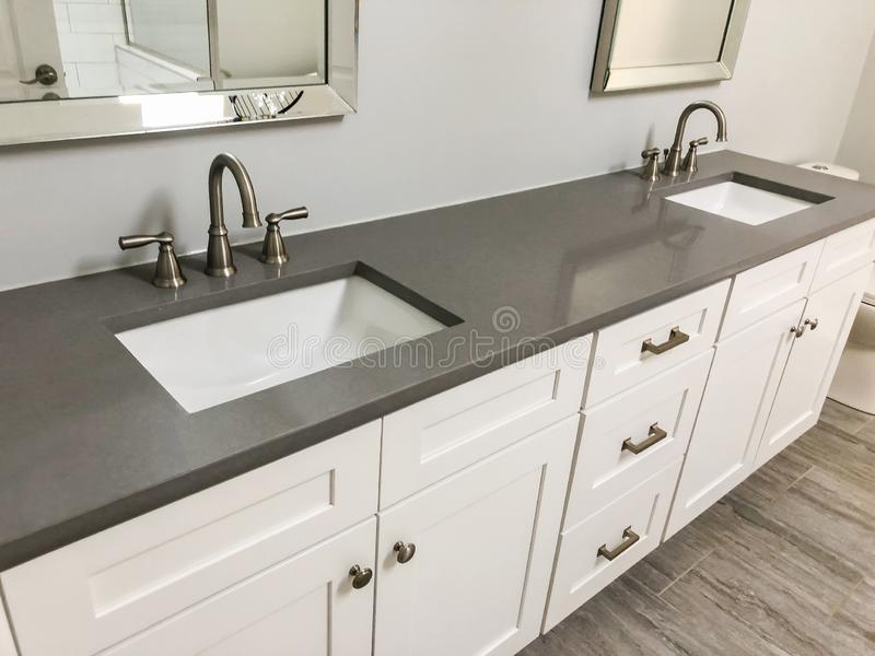 Moderne badkamers met witte kabinetten en kwartscountertop, twee gootstenen en tapkranen met steenvloer royalty-vrije stock foto's