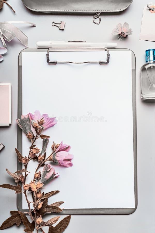 Moderne bedrijfs vrouwelijke Desktopachtergrond met grijs klembord, leeg document blad, parfum, bureauhulpmiddelen en toebehoren stock foto's
