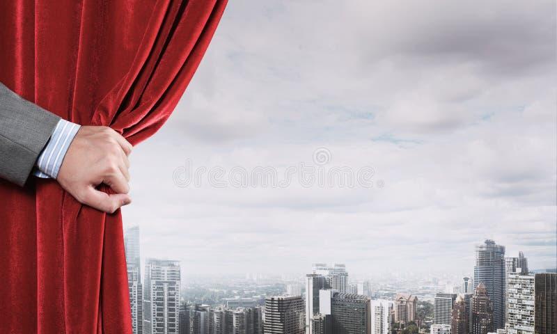 Moderne bedrijfsdiecityscape achter gordijn door zakenmanhand wordt geopend stock foto's