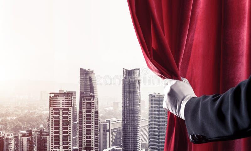 Moderne bedrijfsdiecityscape achter gordijn door zakenmanhand wordt geopend stock fotografie