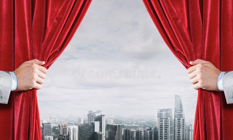 Moderne bedrijfsdiecityscape achter gordijn door zakenmanhand wordt geopend stock foto