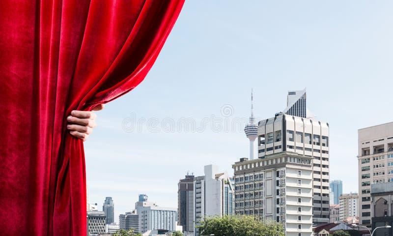 Moderne bedrijfsdiecityscape achter gordijn door zakenmanhand wordt geopend royalty-vrije stock afbeelding