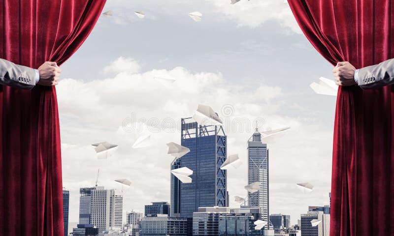 Moderne bedrijfsdiecityscape achter gordijn door zakenmanhand wordt geopend stock afbeeldingen